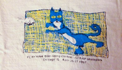 Scamper catching a paperball on a PLAY/Kink contest tee